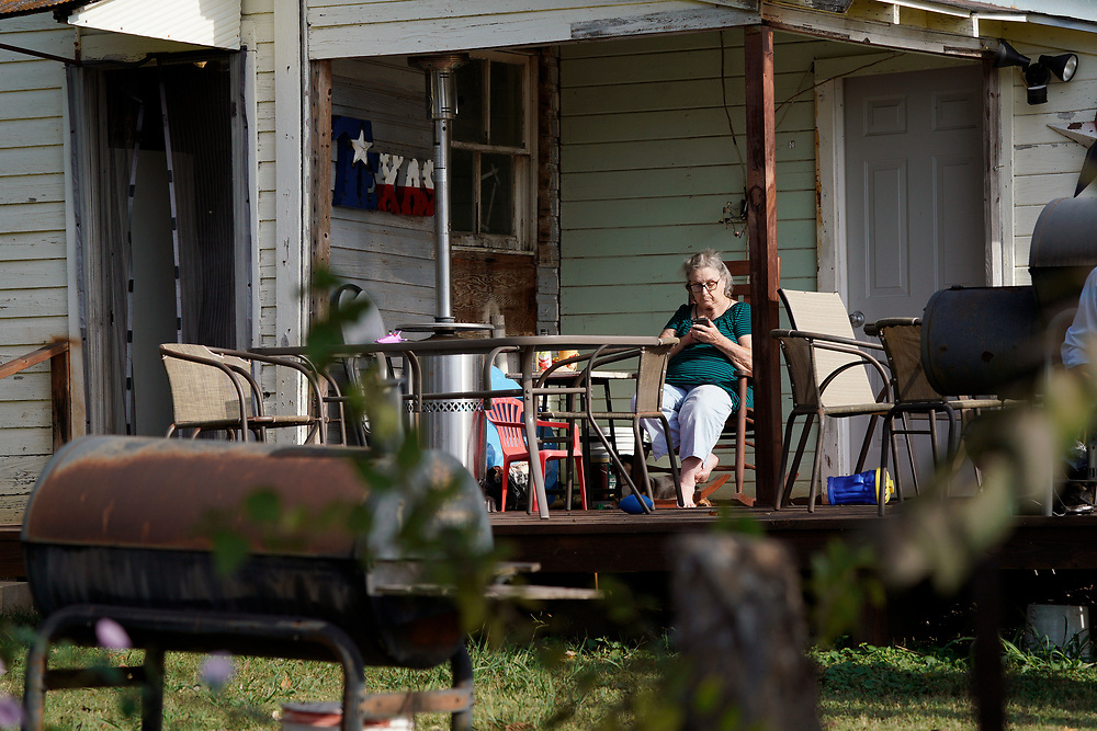 A woman looks at her phone, on her porch next to the site of a shooting at the First Baptist Church of Sutherland Springs, Texas U.S. November 6, 2017.  REUTERS/Rick Wilking