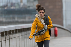 © Licensed to London News Pictures. 09/02/2020. London, UK. A woman walks across London Bridge during windy weather this morning. Rain and windy weather is forecast today as Storm Ciara reaches the capital. Photo credit: Vickie Flores/LNP