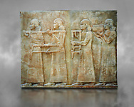 Stone relief sculptured panel of two servants. Facade L. Inv AO 19879 from Dur Sharrukin the palace of Assyrian king Sargon II at Khorsabad, 713-706 BC.  Louvre Museum Room 4 , Paris .<br /> <br /> If you prefer to buy from our ALAMY PHOTO LIBRARY  Collection visit : https://www.alamy.com/portfolio/paul-williams-funkystock/ancient-assyria-antiquities.html  Refine search by adding background colour, place, subject, museum etc into the LOWER SEARCH WITHIN GALLERY box to <br /> <br /> Visit our ANCIENT ASSYRIAN PHOTO COLLECTIONS for more photos to download or buy as wall art prints https://funkystock.photoshelter.com/gallery-collection/Ancient-Assyrian-Art-Artefacts-Antiquities-Historic-Sites-Pictures-Images-of/C0000cjRqQyJjLag