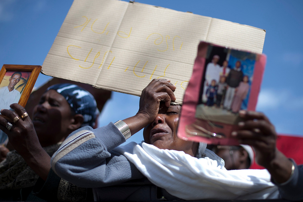 Israelis of Ethiopian descent hold up pictures of their relatives as they take part in a demonstration outside Prime Minister Netanyahu's Office in Jerusalem on April 3, 2011. The protesters called the Israeli government to bring their relatives living in Ethiopia to Israel.