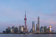 View of the futuristic architecture and the skyline of the buildings of Lujiazui under a moody sky at sunrise, Shanghai, China