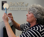 Bank of Belleville Executive Assistant Carol Lengerman takes pictures with her smartphone as employees of Huffman Security, out of Arnold, Missouri, moved bank vaults, cabinets, safety deposit boxes and more from the old site of Bank of Belleville to the new location at 215 South Illinois Street. Belleville police officers were helping guard both the old and new banks, and accompanied each of the Huffman moving trucks on the road. The bank boasts the newest high-tech security and energy conservation systems, and has redundant power supplies in case of a power outage. The bank will open for business at the drive-thru windows at 7:45 a.m. on Monday, and the lobby opens at 9 a.m. -- regular banking hours.