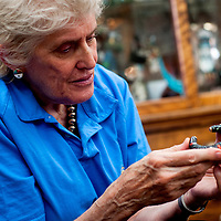 051513       Cable Hoover<br /> <br /> Author Lois Sherr Dubin examines a bracelet made by Lee A. Yazzie Wednesday at Tanner's Gallery in Gallup.