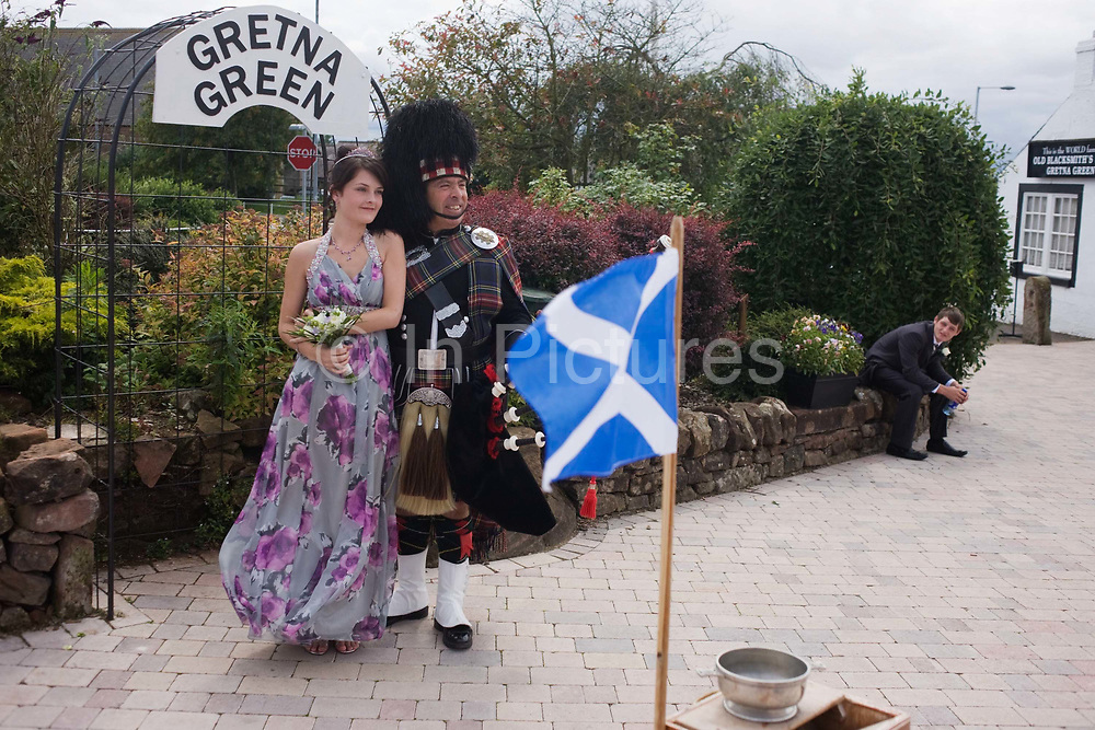 As a young man looks on, a young girl poses with a Scottish piper in Gretna Green where Britain's wedding couples converge for a quickie marriage. Gretna Green is one of the world's most popular wedding destinations; hosting over 5000 weddings each year or one of every six Scottish weddings. Gretna's famous runaway marriages began in 1753 when an Act of Parliament, Lord Hardwicke's Marriage Act, was passed in England, which stated that if both parties to a marriage were not at least 21 years old, then consent to the marriage had to be given by the parents. This Act did not apply in Scotland, where it was possible for boys to get married at 14 and girls at 12 years old with or without parental consent.