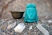 Blue Yoga Avatar statue and metal bowl etched with a sacred mandala set on stone with crystals in an outdoor altar. Charging quartz crystals in the Sierra Mountains. GRATITUDE