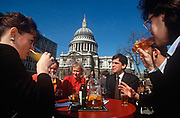 A group of 1990s work colleagues drink outside in summer sunshine, beneath the dome of St. Pauls Cathedral, in the City of London aka The Square Mile, the capitals financial centre, on 20th June 1993, in London, England.