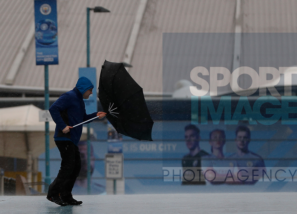 A fans struggles with his umbrella after the Premier League match between Manchester City and West Ham United was postponed because of weather conditions at the Etihad Stadium, Manchester. Picture date: 9th February 2020. Picture credit should read: Darren Staples/Sportimage