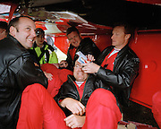 Pilots of the Red Arrows, Britain's RAF aerobatic team shelter under Hawk wing during airshow rain shower.