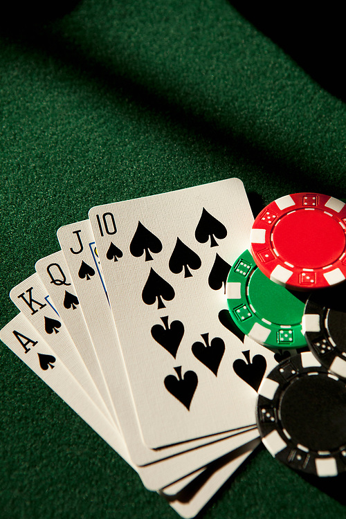 A royal flush poker hand in spades sitting on a green felt table with poker chips