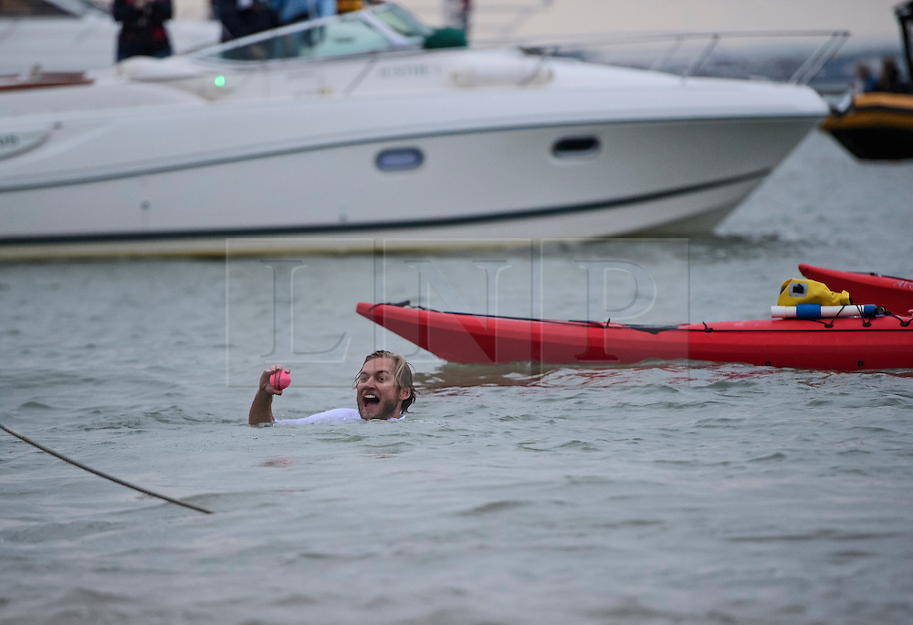© Licensed to London News Pictures. 18/09/2016. Portsmouth, UK. The ball being retrieved from the water. Teams take part in the  Bramble Bank Cricket Match in the middle of The Solent strait on September 18, 2016. The annual cricket match between the Royal Southern Yacht Club and The Island Sailing Club, takes place on a sandbank which appears for 30 minutes at lowest tide. The game lasts until the tide returns. Photo credit: Ben Cawthra/LNP