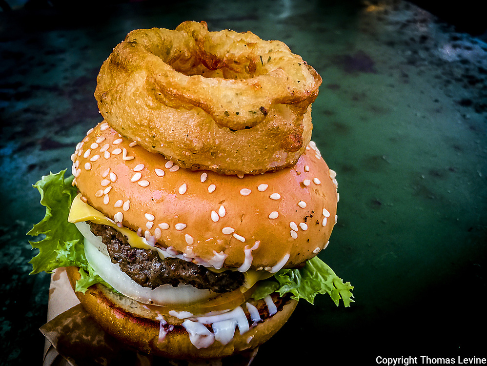 Cheeseburger topped with one large onion ring. Dark Background, moody shot. (iPhone)