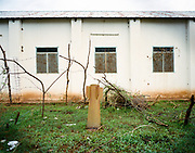 """NUBA MOUNTAINS, SUDAN – JUNE 9, 2018: An unexploded bomb can be seen on the property of the former State Hospital in Kouda, where four parachute bombs were dropped in 2014. Miraculously, none of the ordinances exploded, and can still be seen protruding from the ground surrounding the hospital compound.<br /> <br /> In 2011, the government of Sudan expelled all humanitarian groups from the country's Nuba Mountains. Since then, the Antonov aircraft has terrorized the Nuba people, dropping more than 4,080 bombs on hospitals, schools, marketplaces and churches. Today, vestiges of the Antonov riddle the landscapes of daily life, where more than 1 million Nuba live in famine conditions – quietly enduring the humanitarian blockade intended to drive them out of the region. The skies are mostly clear. Yet the collective memory of the bombings remains an open wound, and the Antonov itself a persistent threat. So frequent were the attacks that the Nuba nicknamed the high flying aircraft and its dismal hum: """"Gafal-nia ja,"""" they would declare, running to the hillsides. """"The loss of appetite has come."""""""