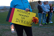 """On May 2, Urula Carpenter, a neighbor of both Diren Dede and Markus Kaarma, and a former German exchange student to the U.S., holds a sign written in German at Dede's candlight vigil that translates to mean, """"Missoula is morning for Diren."""" Kaarma is accused of shooting and killing Dede in his garage on April 27, 2014."""