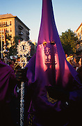 """Las Cigarreros Hermandad, Seville, Andalusia, Spain...Semana Santa de Sevilla, Catholic Holy Week from Palm Sunday to Easter Sunday, is one of the most important traditional, cultural and spiritual events in Seville. The origins of the penitential Holy Week in Seville are to be found in the late Middle Ages. At the heart of Semana Santa are the brotherhoods (Hermandades y Cofradias de Penitencia).  At the centre of each procession are the pasos, an image or set of images set atop a movable float of wood. When a brotherhood has three pasos, the first one would be a sculpted scene of the Passion or an allegorical scene, known as a misterio (mystery); the second an image of Christ and the third an image of the Virgin Mary known as a dolorosa. Many sculptures are of great antiquity and considered artistic masterpieces. A total of 60 penitential processions are organized by hermandades and cofradías, religious brotherhoods. Members precede the pasos dressed in penitential robes and hoods. Sometimes accompanied by brass bands. They take designated routes from home churches and chapels to the Cathedral and back again. Improvised flamenco songs """"saetas"""" are sung to the processions from balconies. The marchers are often accompanied by brass bands, cappella choirs, or a drum and trumpet (historical traditions for a poorer neighborhood)"""
