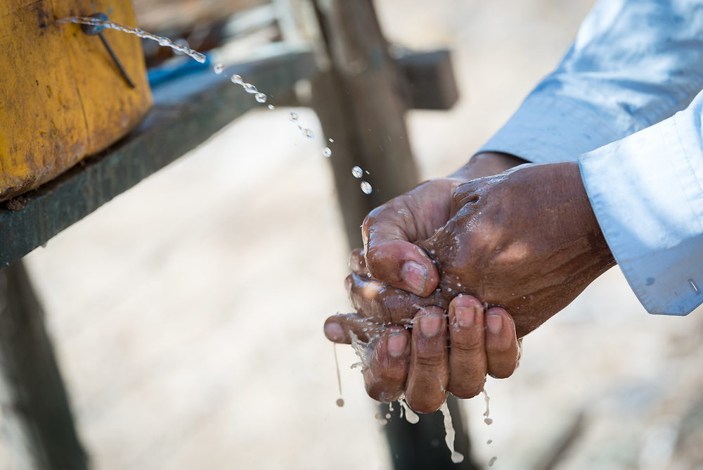 27 January 2019, Micha kebele, Seweyna woreda, Bale Zone, Oromia, Ethiopia: A man washes his hands before a meal. To save water in an area where it is scarce, a small hole has been made in the jerry can, blocked by a nail when the can is not in use.