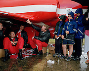 Pilots of the 'Red Arrows', Britain's Royal Air Force aerobatic team take shelter under a scale model of Hawk jet during airshow