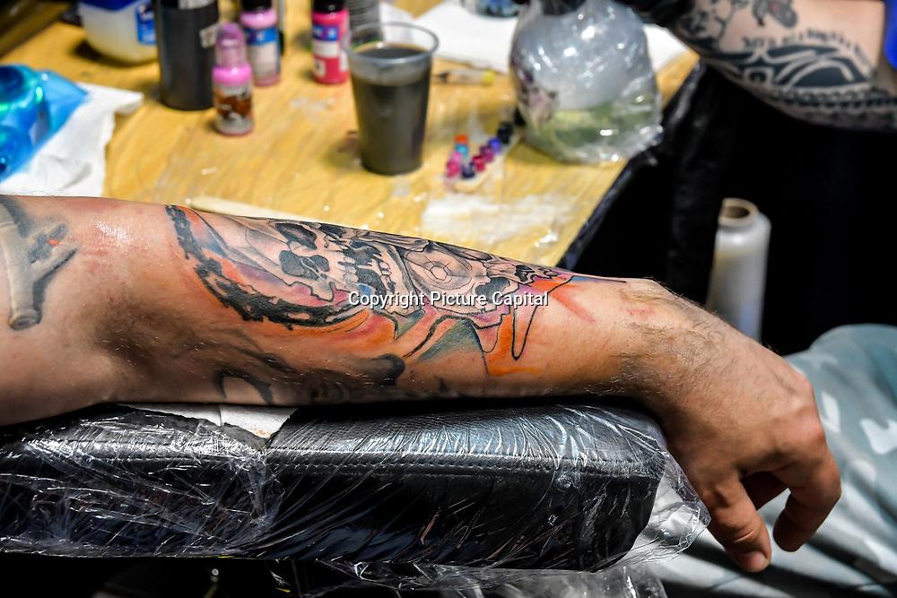 Juzek Ink Tattoo artist tattoo a client at The Great British Tattoo Show, London, UK