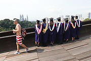 A man passes a group of graduates posing for photographs on Henderson Waves pedestrian bridge, Singapore.