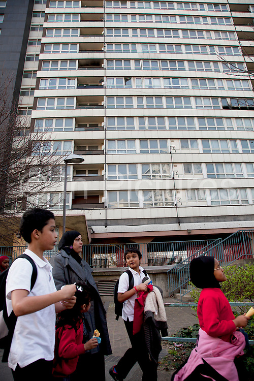 Scene as children head home after school in Carpenters Estate near to the 2012 London Olympic Park in East London. Residents in this area are concerned for many reasons including living in the shadow of the mostly disliked steel tower and the possible threat that the entire estate site may be sold off to UCL (University College London). People in this area generally feel very negative towards the Olympics, which they feel is not going to benefit them at all. Meanwhile the new shopping complex which is next to their estate, there are high end shops selling goods they simply cannot afford.