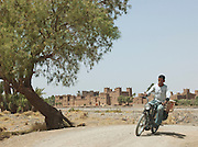 A man on a moped speeds down a road, in front of a kasbah on the banks of a dried river in the Skoura Oasis in Morocco