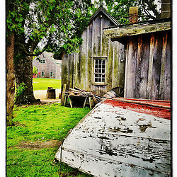 """A wooden skiff behind the Cooper's shed at Strawbery Banke Museum in Portsmouth, New Hampshire. iPhone photo - suitable for print reproduction up to 8"""" x 12""""."""