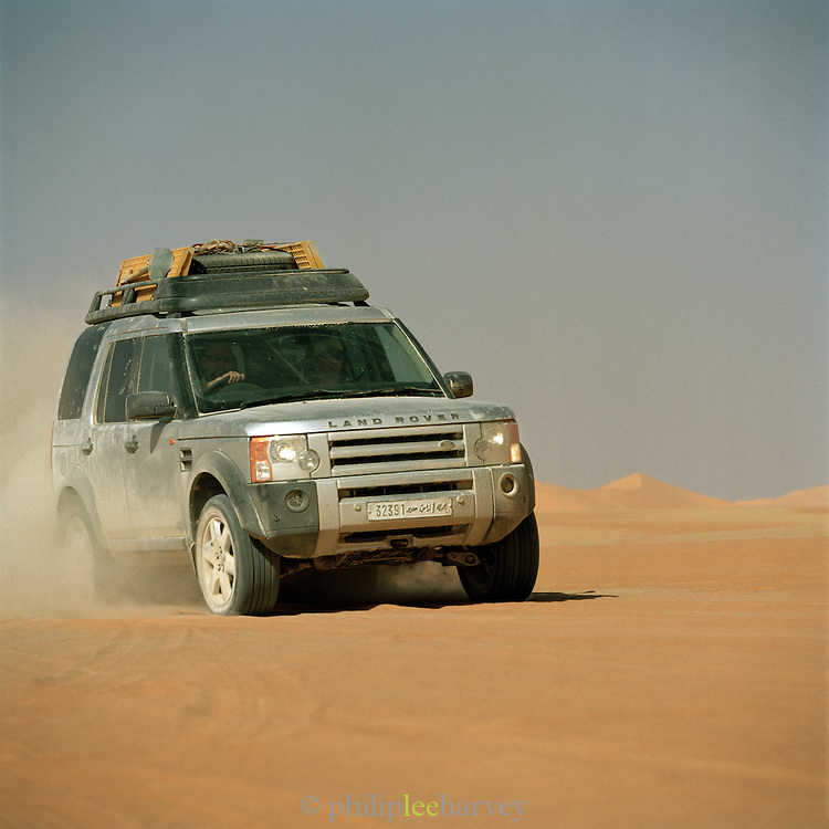 4x4 Landrover Discovery driving through a mixture of volcanic ash and sand in the Sahara desert, Libya