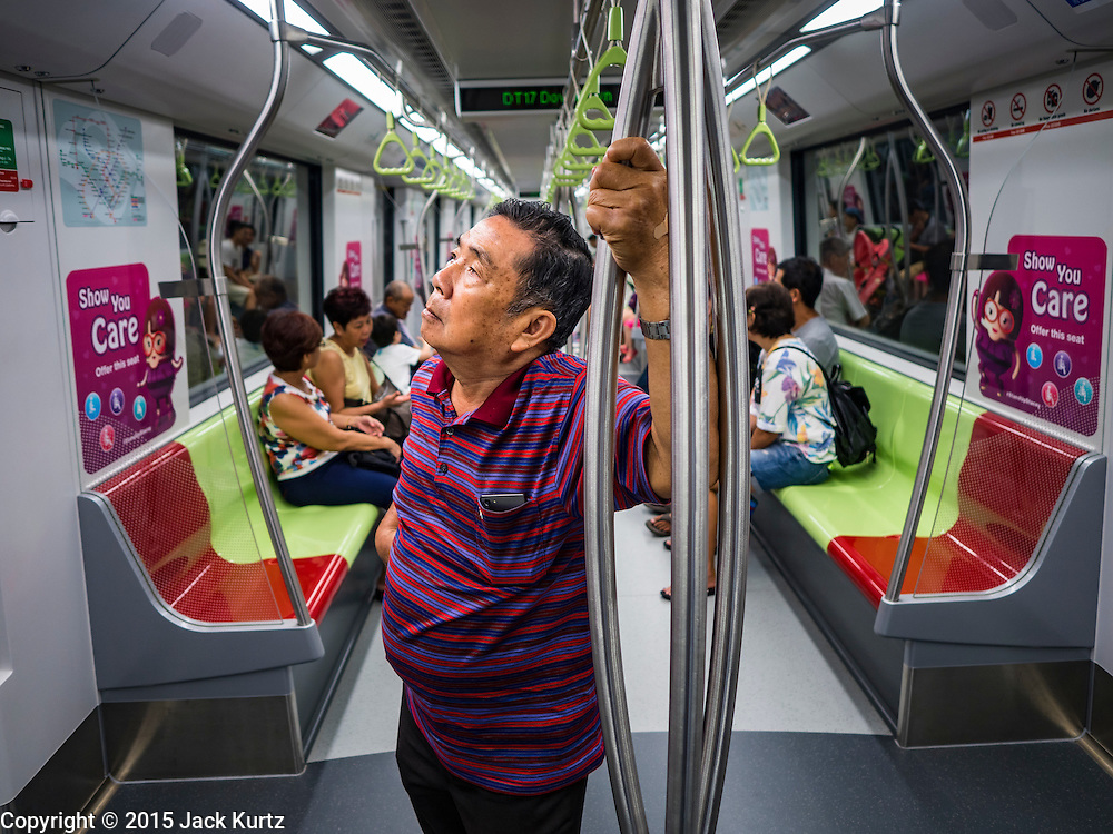 """27 DECEMBER 2015 - SINGAPORE, SINGAPORE: A man studies the subway map while he rides the newly expanded Downtown Line on its first day of service in Singapore. Singapore opened the extension of the Downtown Line on its subway system Sunday. The extension is a part of Singapore's plans to make the city-state a """"car lite"""" metropolis with plans to double the current subway to more than 360 kilometers of track by 2030. The government plans to have 80% of homes within a 10 minute walk of a subway station.    PHOTO BY JACK KURTZ"""