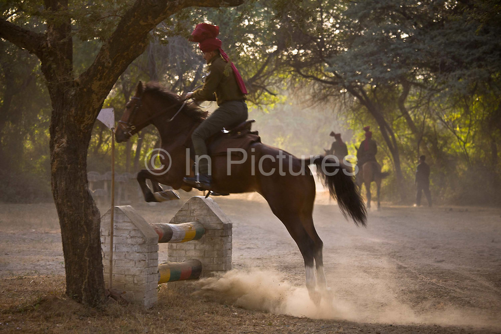 Presidential Bodyguard soldier in early morning dust and mist filled horsemanship practice, consisting of jumping, daredevil riding and other such activities at the PBG's barrack training grounds. This a regular activity as it requires the riders to perfect their horse riding skills and maneuvers for their official duties at ceremonial events.  The PBG is the Indian Army's preeminent regiment founded in 1773 during the British occupation, this handpicked unit began with a mere 50 men and today stands at 160 soldiers plus 50 support staff. It has a dual role, both as a ceremonial guard for the President of India, with all its finery at important state functions, as well as an elite operational unit for the Indian Army which has seen action in many battle fronts, in particular the on going disputed region of Kashmir.