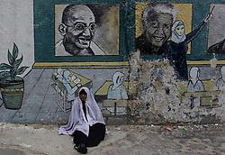 Dec. 10, 2013 - Gaza City, Gaza Strip, Palestinian Territory - A Palestinian woman sits under a mural depicting late South African leader President Nelson Mandela in Gaza city, on Dec. 10, 2013  (Credit Image: © Ashraf Amra/APA Images/ZUMAPRESS.com)