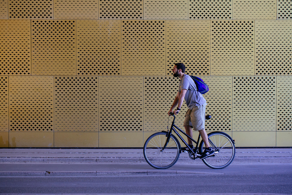 A man in shorts, t-shirt with backpack riding a bicycle.<br /> <br /> SELF PROPELLED is portrait study of Copenhagen and its residents.