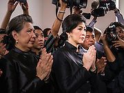 19 OCTOBER 2014 - BANG BUA THONG, NONTHABURI, THAILAND: RATCHANEE WIRIYACHAI, (left) widow of Apiwan Wiriyachaiat, and YINGLUCK SHINAWATRA, former Prime Minister of Thailand, at Apiwan Wiriyachai's cremation at Wat Bang Phai in Bang Bua Thong, a Bangkok suburb, Sunday. Apiwan was a prominent Red Shirt leader. He was member of the Pheu Thai Party of former Prime Minister Yingluck Shinawatra, and a member of the Thai parliament and served as Yingluck's Deputy Prime Minister. The military government that deposed the elected government in May, 2014, charged Apiwan with Lese Majeste for allegedly insulting the Thai Monarchy. Rather than face the charges, Apiwan fled Thailand to the Philippines. He died of a lung infection in the Philippines on Oct. 6. The military government gave his family permission to bring him back to Thailand for the funeral. His cremation was the largest Red Shirt gathering since the coup.     PHOTO BY JACK KURTZ