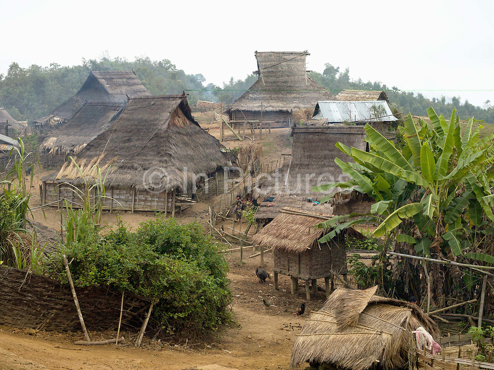 An Akha Nuquie village with traditional grass roofed houses in remote Ban Peryenxangmai village, Phongsaly province, Lao PDR. Lying in a cleared patch of the surrounding forest, typical Akha villages have houses which are made of bamboo and wood with thatched roofs and house 'horns' although increasingly houses now have corregated iron roofs. The Akha favour remote locations above the plains and valleys, generally 1000-1500 m high where there is plenty of forest cover.