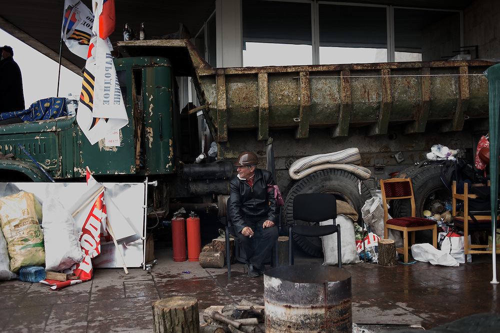 A pro-Russia activist takes guard at one of the entrances of Donbass Regional Government building in central Donetsk. Barricades around the building, occupied since the past weekend, have been fortified throughout the day, as the ultimatum given by the government in Kiev for the activists to abandon the building within 48 hours, is approaching its deadline.