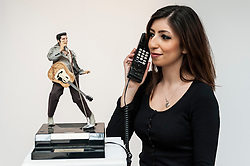 © Licensed to London News Pictures. 26/02/2016. London, UK. A Sotheby's staff member shows a dancing Elvis telephone from the Duchess' collection of Elvis Presley memorabilia.  Property from the personal collection of Deborah, Duchess of Devonshire (1920-2014), will be offered for sale at Sotheby's on 2 March,  The youngest of the Mitford Sisters, the Duchess was the chatelaine of Chatsworth, one of England's greatest stately homes, and at the heart of British rural, cultural and political life.  The proceeds of the items in the eclectic collection are expected to realise £500,000 to £700,000. Photo credit : Stephen Chung/LNP
