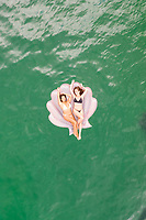 Aerial view of attractive girls with an inflatable at Gordons Bay, Sydney. Australia.