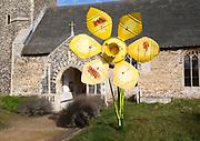 Large yellow metal daffodils artwork in churchyard of village parish church and  Saint Mary, Henstead, Suffolk, England, UK