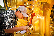 """05 JULY 2011 - BANGKOK, THAILAND:     A man uses gold spray paint to touch up a Buddha statue for sale on Bamrung Muang Street in Bangkok. Thanon Bamrung Muang (Thanon is Thai for Road or Street) is Bangkok's """"Street of Many Buddhas."""" Like many ancient cities, Bangkok was once a city of artisan's neighborhoods and Bamrung Muang Road, near Bangkok's present day city hall, was once the street where all the country's Buddha statues were made. Now they made in factories on the edge of Bangkok, but Bamrung Muang Road is still where the statues are sold. Once an elephant trail, it was one of the first streets paved in Bangkok, it is the largest center of Buddhist supplies in Thailand. Not just statues but also monk's robes, candles, alms bowls, and pre-configured alms baskets are for sale along both sides of the street.       PHOTO BY JACK KURTZ"""