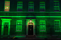 London, UK. 13 June, 2019. 10 Downing Street is lit in green to mark the second anniversary of the Grenfell Tower fire on 14th June 2017 in which 72 people died and over 70 were injured.