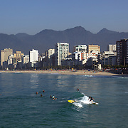 Early morning surfers at Ipanema beach catch a wave as the sunrise catches the light of the surrounding beachfront properties. Ipanema beach, Rio de Janeiro, Brazil. 9th July 2010. Photo Tim Clayton..The beaches of Rio de Janeiro, provide the ultimate playground for locals and tourists alike. Beach activity is in abundance as beach volley ball, football and a hybrid of the two, foot volley, are played day and night along the length and breadth of Rio's beaches. .Volleyball nets and football posts stretch along the cities coastline and are a hive of activity particularly at it's most famous beaches Copacabana and Ipanema. .The warm waters of the Atlantic Ocean provide the ideal conditions for a variety of water sports. Walkways along the edge of the beaches along with exercise stations and cycleways encourage sporting activity, even an outdoor gym is available at the Parque Do Arpoador overlooking the ocean. .On Sunday's the main roads along the beaches of Copacabana, Leblon and Ipanema are closed to traffic bringing out thousands of people of all ages to walk, run, jog, ride, skateboard and cycle more than 10 km of beachside roadway. .This sports mad city is about to become a worldwide sporting focus as they play host to the world's biggest sporting events with Brazil hosting the next Fifa World Cup in 2014 and Rio de Janeiro hosting the Olympic Games in 2016..