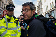 Police officers arrest journalist George Monbiot on Whitehall on 16th October 2019 in England, United Kingdom.  Extinction Rebellion climate activists sit down in the road despite the police imposing a section 14 of the Public Order Act 1986  in effect banning all protest by the group in London.
