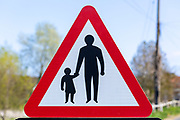 Macro close up Highway Code red triangle road sign warning of pedestrians walking, UK