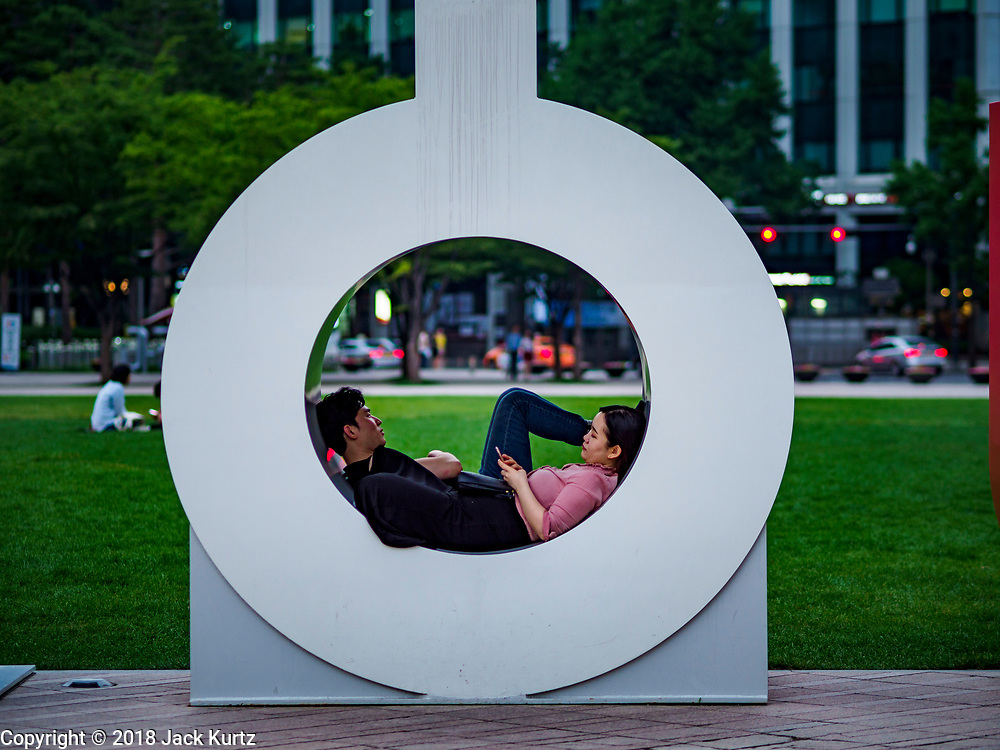 """13 JUNE 2018 - SEOUL, SOUTH KOREA: A couple relaxes in the """"O"""" in the """"Seoul"""" sculpture in front of the Seoul City Hall.       PHOTO BY JACK KURTZ"""