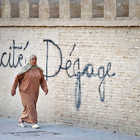 Kairouan, Tunisia 27 October 2011<br /> A Tunisian woman pass by a graffiti against secularism.<br /> Photo: Ezequiel Scagnetti