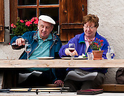 A couple enjoys an outdoor meal with wine in Val di Funes (Villnöß valley) in the Dolomites, Italy, Europe. Puez-Geisler Nature Park (Italian: Parco naturale Puez Odle; German: Naturpark Puez-Geisler) is in Südtirol/South Tyrol/Alto Adige, in the Dolomiti, part of the Southern Limestone Alps, Italy. The Dolomites were declared a natural World Heritage Site (2009) by UNESCO.