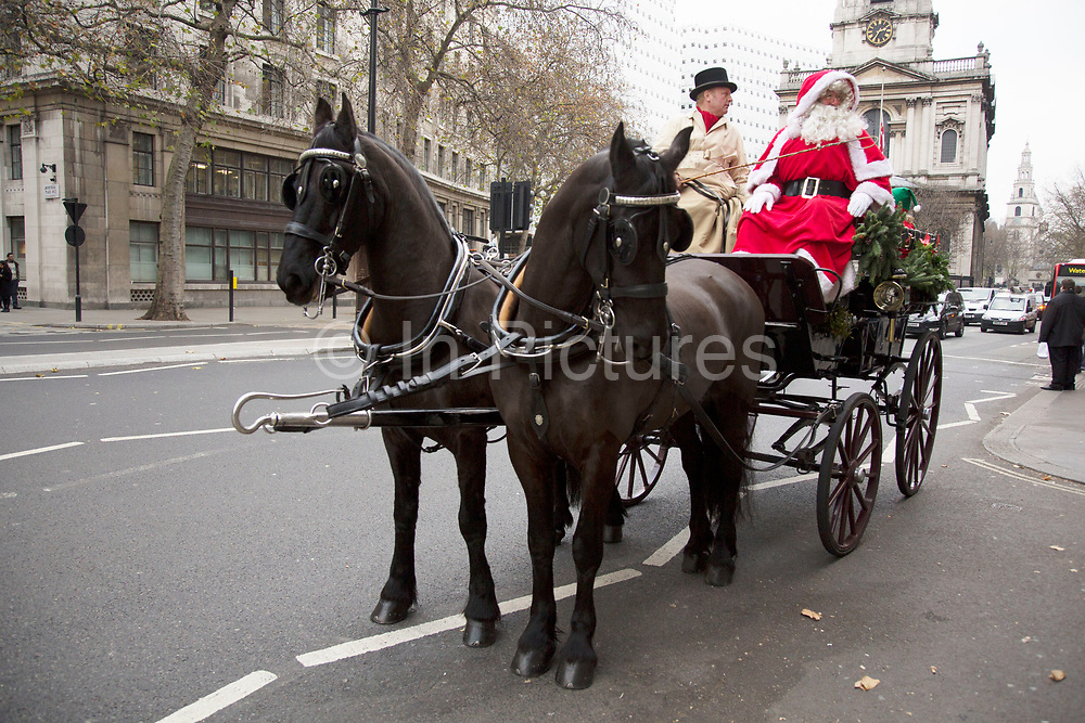 Santa Clause in a horse drawn carriage driving through central London, UK. Surprising members of the public and bringing some Christmas festive atmosphere.