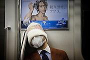 TOKYO, JAPAN, 30 MAY - A salary man sleep in the train with a mask on his face and a wooly hat on his head that could not permit us to know is identity. Just behind, a commercial for a shampoo. May 2012 [FR] Un homme en costume est endormi dans le train. Il porte un masque et un bonnet et laine. Juste derrière lui, une affiche pour un shampoing