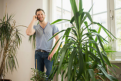 Mid adult man talking on mobile phone in living room and smiling, Munich, Bavaria, Germany