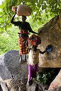 Mother and son climbing the cliff with burdens on their heads in the Bandiagara Escarpment. The Dogon Country is the most visited part of Mali with tourists visiting its tipical  villages that can be located on the cliff, on the sandy plain or in the rocky plateau
