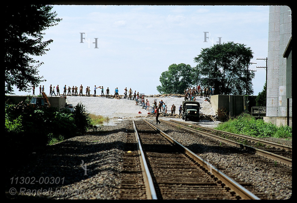 RR tracks run under levee as sandbaggers line top on 8/4/93 in effort to save Prairie du Rocher Illinois