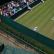 A man takes time out to read a book while Sam Stosur, Australia is in action during her win against Tatjana Malek, Germany, in the second round of the Ladies Singles competition at the All England Lawn Tennis Championships at Wimbledon, London, England on Thursday, June 25, 2009. Photo Tim Clayton.